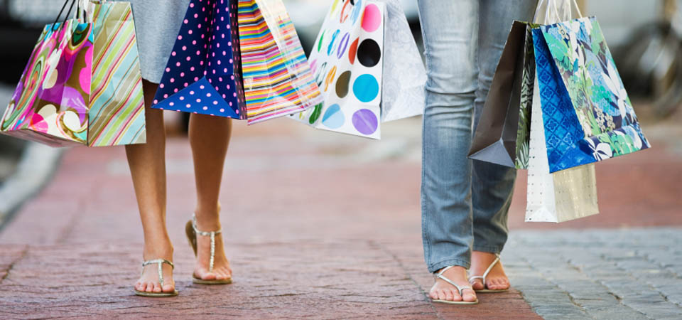 Closeup portrait of two women's legs walking with bags